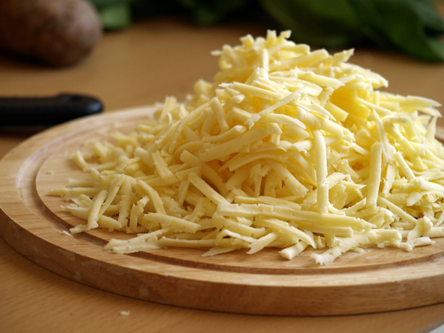 Натертый сыр на доске